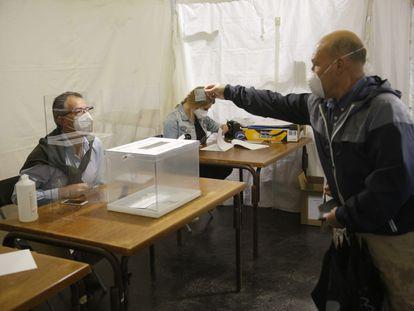 Un votante deposita su papeleta en Ordizia (Gipuzkoa) entre medidas sanitarias y de distancia social.