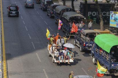 Simpatizantes del ejército pasan cerca de vehículos policiales en una calle en Yangon, este lunes.
