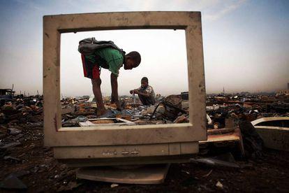Unos niños recogen la parte metálica de una pantalla, en Agbogbloshie, barrio de Accra, Ghana. No se protegen para manipular productos químicos como el mercurio o el plomo. Fotografía de la serie fotográfica 'Vertedero de basura 2.0', de Andrew McConnell.
