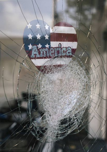 """<b>Las cosas, como son. </b>Una pegatina con la palabra """"América"""" en la ventana rota de un negocio en Kenosha (Wisconsin) el 25 de agosto tras los disturbios contra el racismo se convierte en símbolo del daño que la mentira ha hecho en un país, Estado Unidos, donde incluso su presidente ha difundido bulos."""