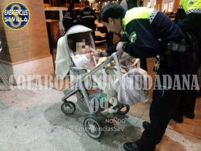 Policía local con la bebé de 14 meses en un bar de Sevilla.