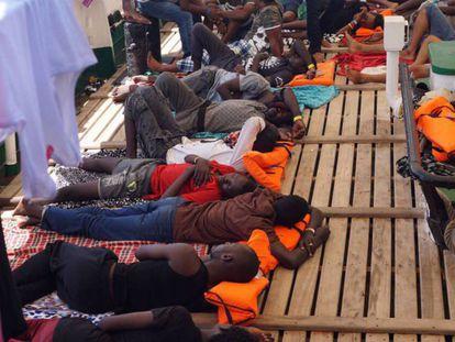 Los rescatados por el 'Open Arms' descansan en la cubierta del buque. En vídeo, los inmigrantes a bordo del barco Open Arms en el Mediterráneo.