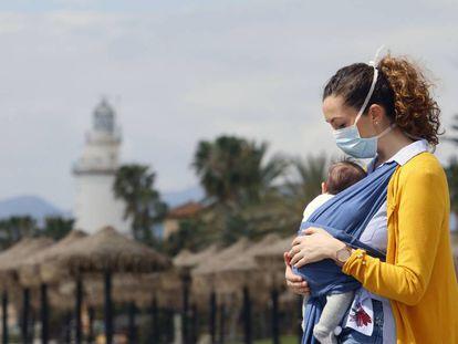 Una mujer protegida con una mascarilla da un paseo con su bebé en la playa de La Malagueta.