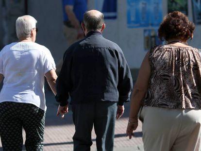 Un grupo de pensionistas cruzan un paso de cebra. En el vídeo, declaraciones de la ministra de Empleo y Seguridad Social, Fátima Báñez.