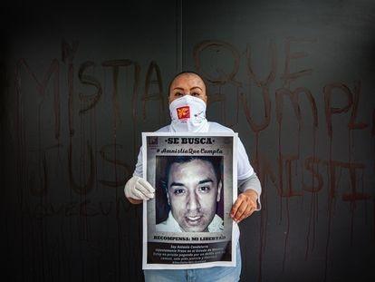Alicia Reyes, madre de Antonio Candelaria, posa con un cartel de su hijo en una protesta por la ley de amnistía.