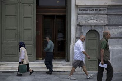 Viandantes, este lunes ante el Banco Central de Grecia en Atenas.