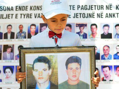 Un niño con las imágenes de dos desaparecidos durante la conmemoración del Día Internacional de los Desaparecidos, en agosto de 2019 en Pristina.