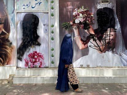Una afgana ataviada con el burka pasa ante los carteles de un centro de belleza, en Kabul.