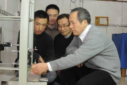 El físico Jun Luo (derecha) y su equipo, junto a uno de sus aparatos.