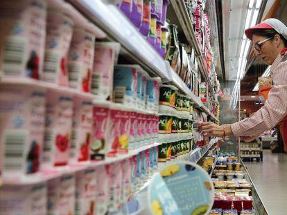 Una reponedora en la sección de lácteos de un supermercado.