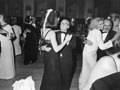 Truman Capote baila con una invitada en El baile en blanco y negro que celebrró en el Hotel Plaza de Nueva York el 28 de noviembre de 1966. A la izquierda, la editora del 'Washington Post' Katherine Graham, invitada de honor en la fiesta. A la derecha, la actriz estadounidense Lauren Bacall baila con el coreógrafo y bailarín Jerome Robbins. |