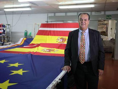 El empresario José Luis Sosa Dias, en su fábrica de banderas junto a insignias de España y de la Unión Europea.