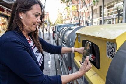 Emma Durán, usuaria de Reciclos, escanea un código QR tras reciclar una botella en Sant Boi.