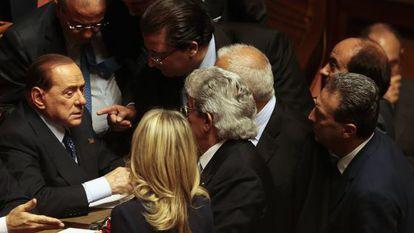 Berlusconi habla con otros senadores en el voto de confianza a Letta.