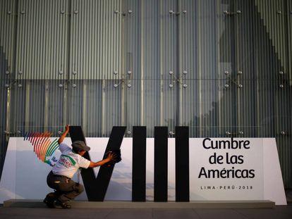 Una mujer limpia el logo de la Cumbre de las Américas en Lima.