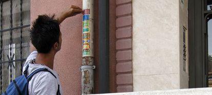 Un joven pone pegatinas de cerrajeros en un portal de la capital.
