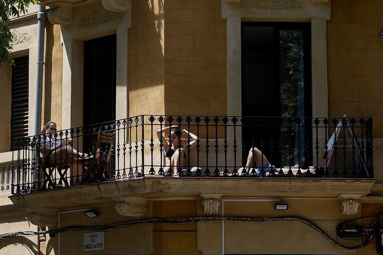 Tres jóvenes toman el sol este viernes en el balcón de su piso del barrio del Eixample de Barcelona.