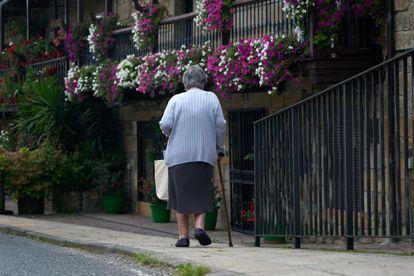 Una mujer pasea por Villacarrido, un pueblo de los valles de Cantabria.