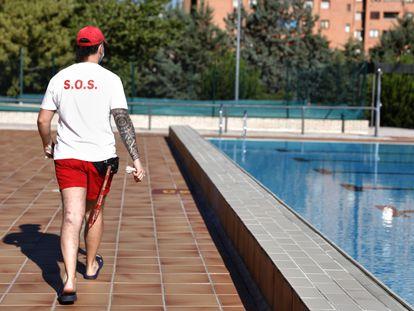 Un socorrista camina por una piscina.