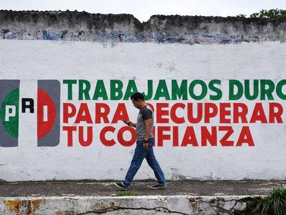 Un hombre camina por una calle del centro de la ciudad de Xalapa frente a un muro promocional del PRI el día 14 de junio de 2018.