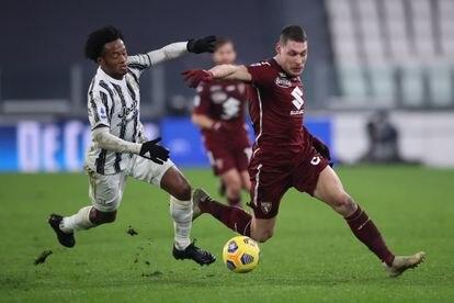 El delantero del Torino Andrea Belotti se lleva el balón ante el juventino Cuadrado.