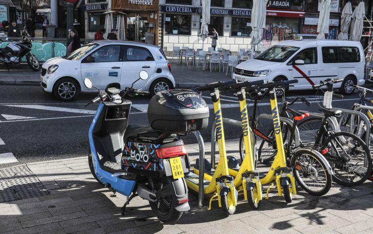 Patinetes, motos eléctricas y coches eléctricos de alquiler, en las calles de Madrid.