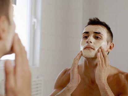 Un hombre se coloca una mascarilla para el cuidado facial.