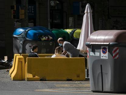 La terraza de un bar en pleno chaflán de la calle Aragón, entre contenedores de basura y reciclaje.