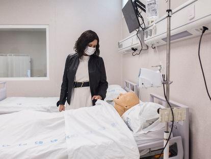 La presidenta de la Comunidad de Madrid, Isabel Díaz Ayuso, observa un maniquí que simula a un paciente durante su visita al Complejo Hospitalario 12 de Octubre, a 6 de abril de 2021, en Madrid (España).