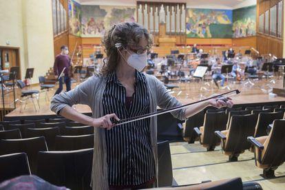 Una de las integrantes de la OSE da resina a su arco antes del ensayo.
