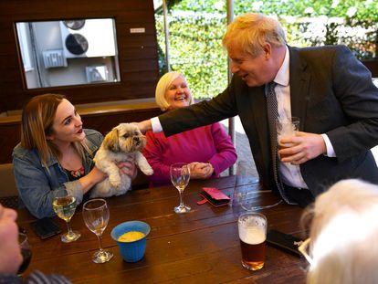 Johnson acaricia al perro de la cliente de un bar, en Wolverhampton el pasado 19 de abril.