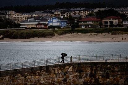 Una persona pasea por el puerto de Foz bajo la fina lluvia.