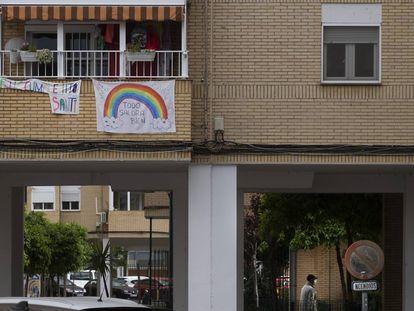 Una pancarta de felicitación de cumpleaños y otra con el arcoiris con las palabras 'Todo saldrá bien' en un edificio de Sevilla.