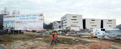 Unos trabajadores caminan por las obras del futuro hospital de Collado Villalba.