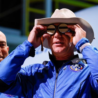 Billionaire American businessman Jeff Bezos wears goggles owned by Amelia Earhart which he carried into space at a post-launch press conference after he flew on Blue Origin's inaugural flight to the edge of space, in the nearby town of Van Horn, Texas, U.S., July 20, 2021. Bezos' brother Mark is on the left. REUTERS/Joe Skipper