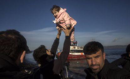Un iraquí, procedente de la ciudad de Mosul (ocupada por el ISIS), sostiene a su hija tras llegar en un pequeño bote, junto a otros 150 refugiados, a la isla de Lesbos este martes.