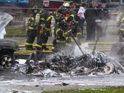 Bomberos de Seattle apagan los restos del helicóptero incendiado
