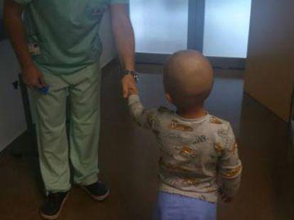 Un sanitario da la mano al niño en el Hospital Universitario de Torrevieja.