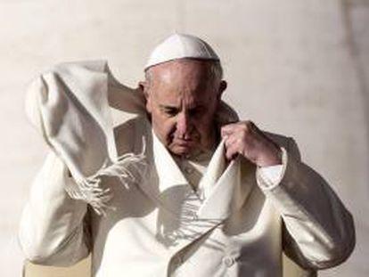 El papa Francisco se coloca la bufanda a su llegada a la plaza de San Pedro del Vaticano para presidir la audiencia general semanal el 8 de enero de 2014. EFE/Archivo
