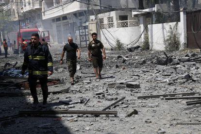 Unos bomberos inspeccionan una zona derruida por un bombardeo, este domingo en ciudad de Gaza.