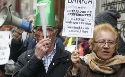 Dos ancianos con carteles proestan frente a la Audiencia Nacional.
