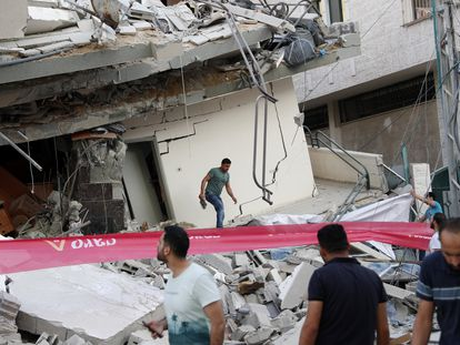 Varias personas inspeccionan este lunes un edificio residencial destruido en la franja de Gaza por un ataque aéreo israelí.