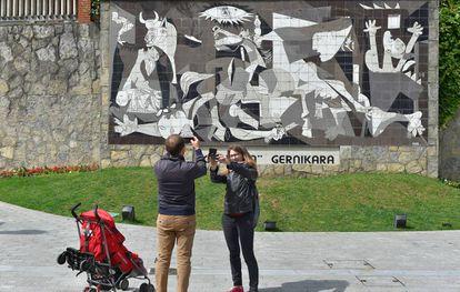 Una pareja toma una foto de una réplica del 'Guernica' de Picasso.