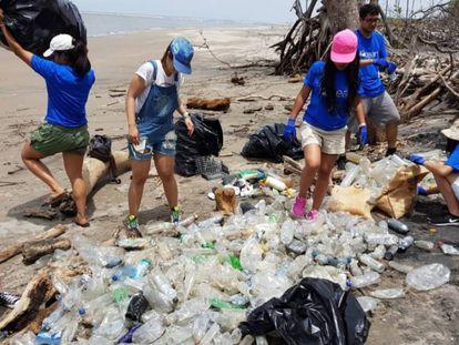 Un grupo de adolescentes limpia la playa de la Isla Tasajera en El Salvador.