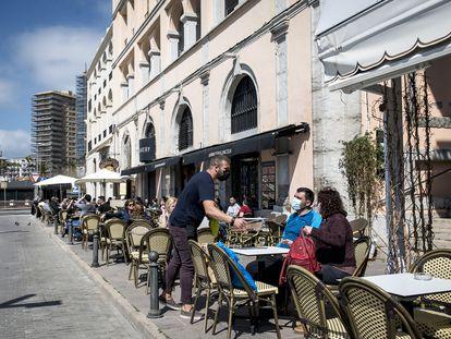 Un camarero protegido con mascarilla en un restaurante de Palamós, Girona, en marzo.