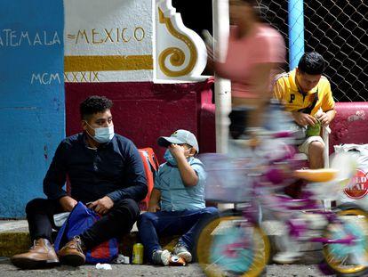 Un migrante hondureño y su hijo esperan este martes a cruzar el puente en Tuxtla Chico, al sur de México, tras ser expulsados de EE UU bajo el Título 42.
