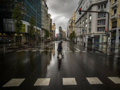 Una mujer cruza la Gran Vía de Madrid, desierta por el confinamiento, el 23 de marzo de 2020.