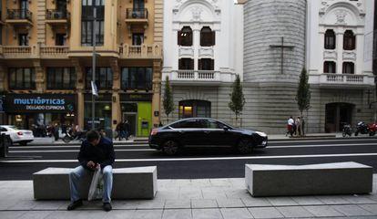 Un hombre se sienta en un nuevo banco de la Gran Vía; al fondo, el Real Oratorio del Caballero de Gracia.