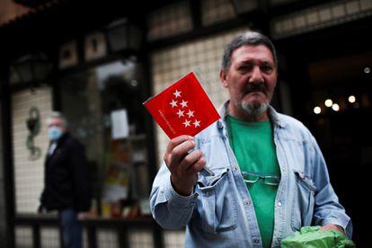 Un hombre muestra una mascarilla FPP2 que está entregando gratuitamente la Comunidad de Madrid tras recogerla en una farmacia este miércoles durante la pandemia.
