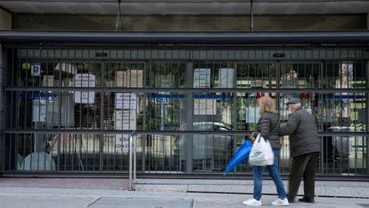 Dos personas frente al centro de salud Doctor Cirajas cerrado, este jueves en Madrid.